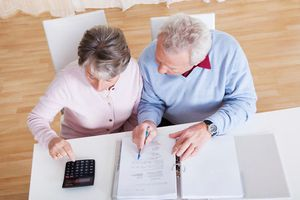 Older couple looking at financial information with a calculator at a table