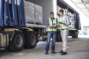 two workers looking at clipboards with a loaded truck behind them