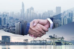 Businessmen are shaking hands to agree to a business deal success business of logistics industrial container cargo freight ship.