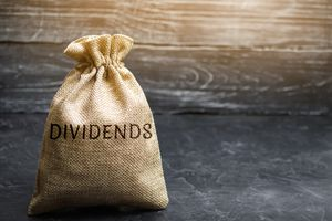 Money bag with the word Dividends. A dividend is a payment made by a corporation to its shareholders as a distribution of profits.