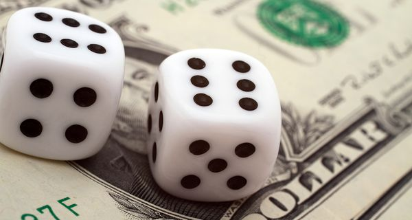 Two dice with six on a dollar note