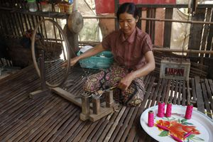 Microfinance client spinning silk in her home