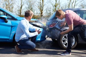 Two drivers look at car damage after accident