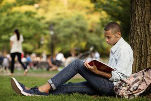 Side view of man studying while sitting by tree trunk in campus