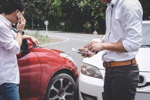 Men Using Mobile Phones By Broken Cars On City Street