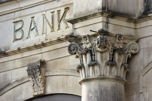 """Bank exterior, showing the decorative top of a column and the word """"BANK"""" carved into the stone."""
