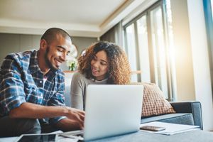 Couple at home looking at investments on laptop