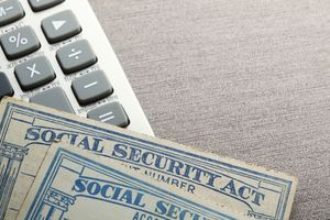 Two social security cards rest on top of a calculator.