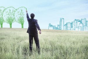Businessman drawing imaginary colored trees and a skyline in a field