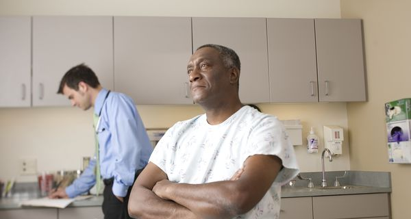 Black man with arms crossed in patient gown while White doctor writes in file