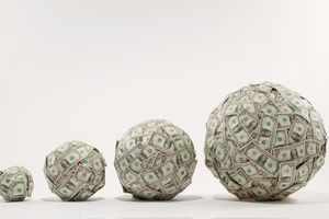 Growing balls of money represent the historical evolution of capitalism through three different epochs.