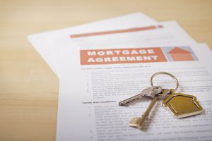 House keys and mortgage loan agreement on desk, close up.