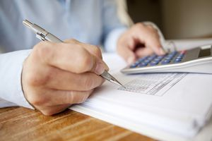 An accountant using a calculator and a pen.