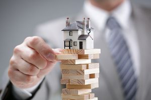 A man's hand is removing a wooden block from a precarious stack supporting a toy house.