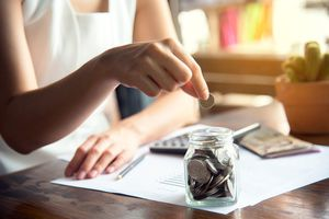An hand of female putting coin in jar with money stack.
