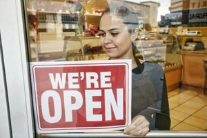 Store owner puts open sign in store window