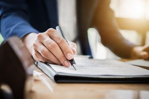 Estate Agent Gives Pen and Documents Agreement With Customer To