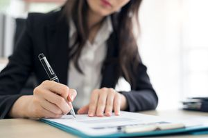 woman making notes with a pen on a paper on a clipboard