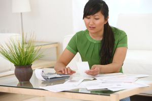 Photo shows woman with a desk full of paperwork to indicate that refinancing a mortgage is complex.