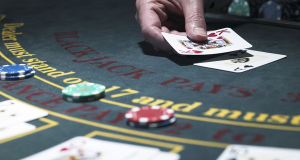 Male croupier holding card at Blackjack table.