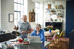 Senior woman using laptop and smiling as man serves breakfast