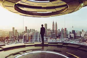 Businessman Looking at Cityscape While Standing in Modern Office