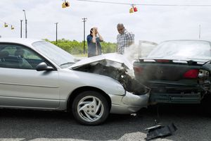 Two cars in an accident with drivers looking at damage