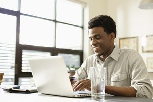 Young man at laptop, calculating loan costs
