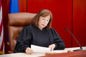 Judge in a courtroom reading documents