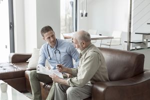 Senior man on meeting with insurance agent at home