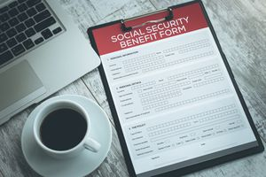 A Social Security benefit form on a desk, with a laptop computer and a cup of coffee.