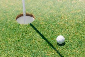 A golf ball near the hole on the green