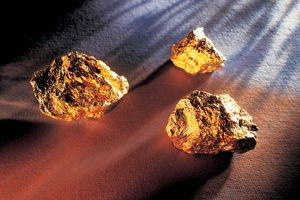 Three large gold nuggets on a table.