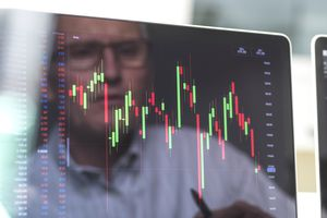 Reflection of a stock trader viewing a company's share price