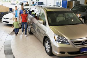 Family looking at new cars in a showroom