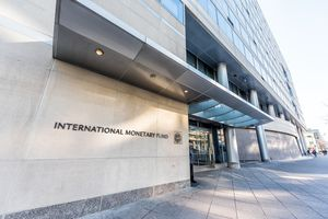 IMF entrance with sign of International Monetary Fund, concrete architecture building wall security guard doors