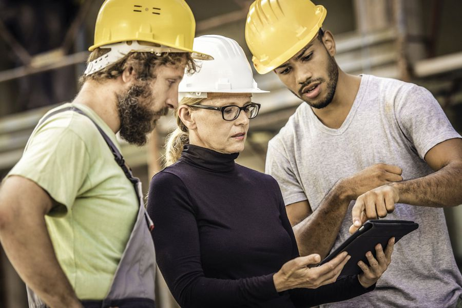 Two male construction workers in hardhats consult with a female architect in hardhat on plans she holds.
