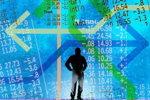 Man looking at confusing arrows and stock market data