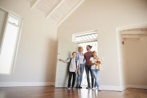 Family opening door and walking in empty lounge of new home.