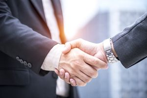 A businessman shaking hand with business partner investment for success plan.