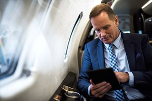 Businessman sitting in a private plane using a tablet