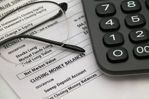 A financial statement with glasses and calculator on the desk.