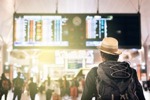 Man Looking at Illuminated Arrival Departure Board