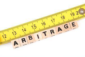 A ruler measuring wood blocks that read arbitrage
