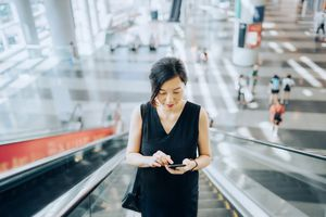 Woman looking at her phone while riding an escalator.