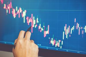 Cropped hand of stockbroker pointing at graph on screen.