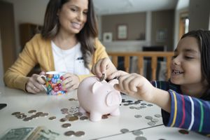 Mother watching son place coins in piggy bank.
