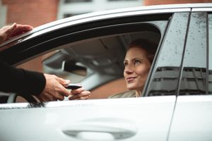 Car rental dealer is giving a car key to a smiled woman who is sitting in the car