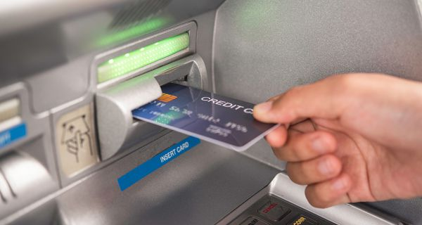 Cropped Hand Inserting Credit Card in ATM Machine