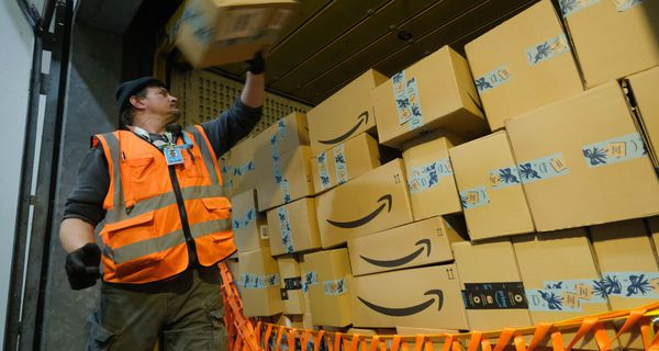 A worker loads a truck with packages at an Amazon packaging center
